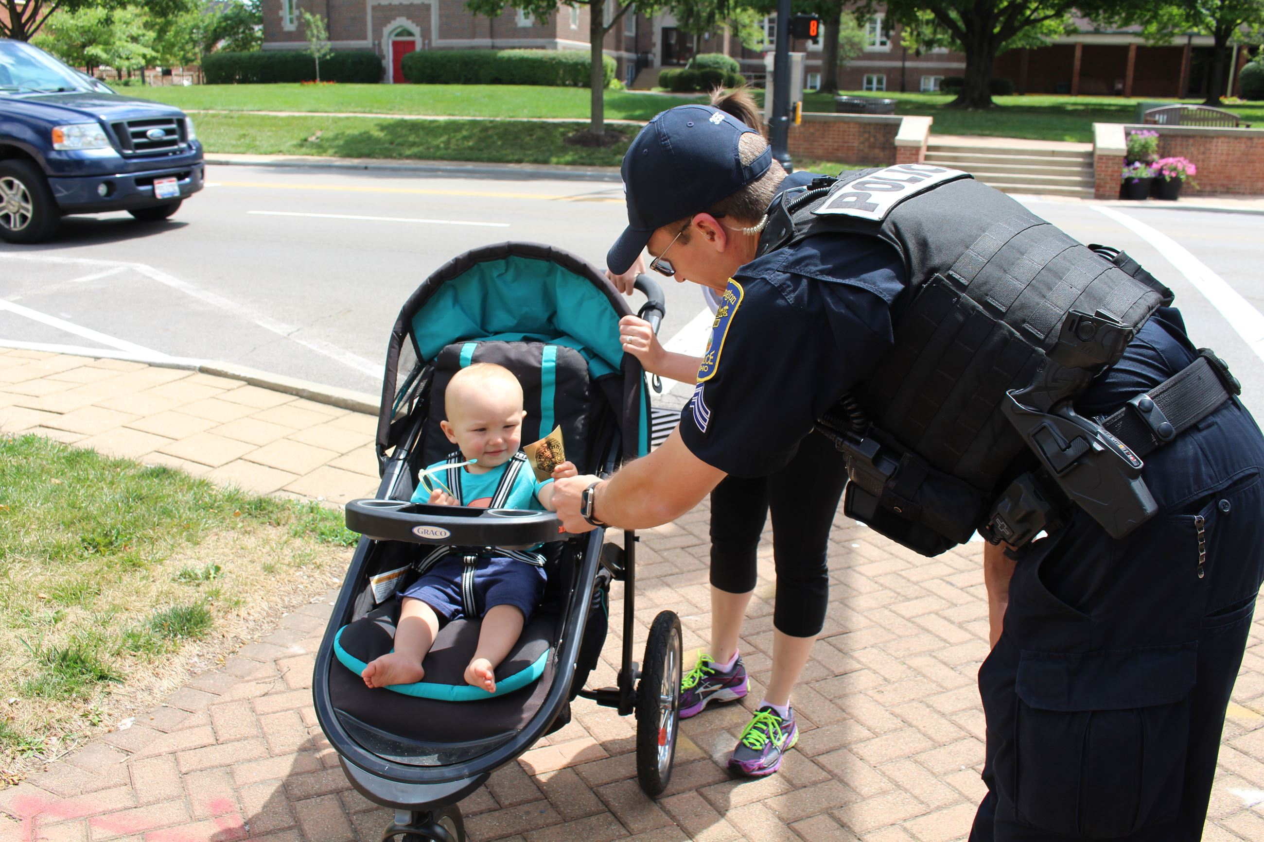 Sgt Mette gives a badge sticker to a baby